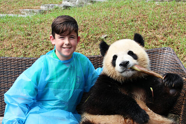 Children play with Panda at Chengdu Research and Base of Giant Panda